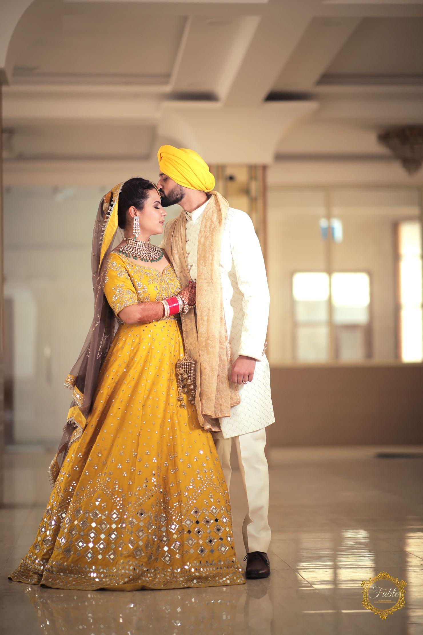 punjabi groom kissing on bride's forehead