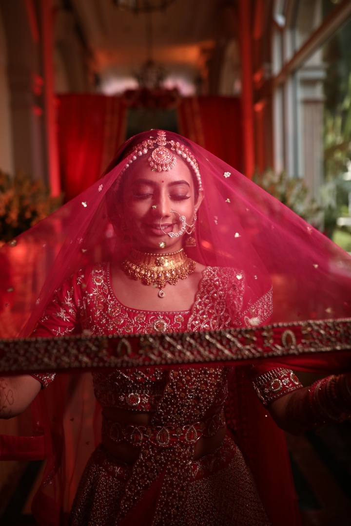 stunning bride in pink poses with her veil