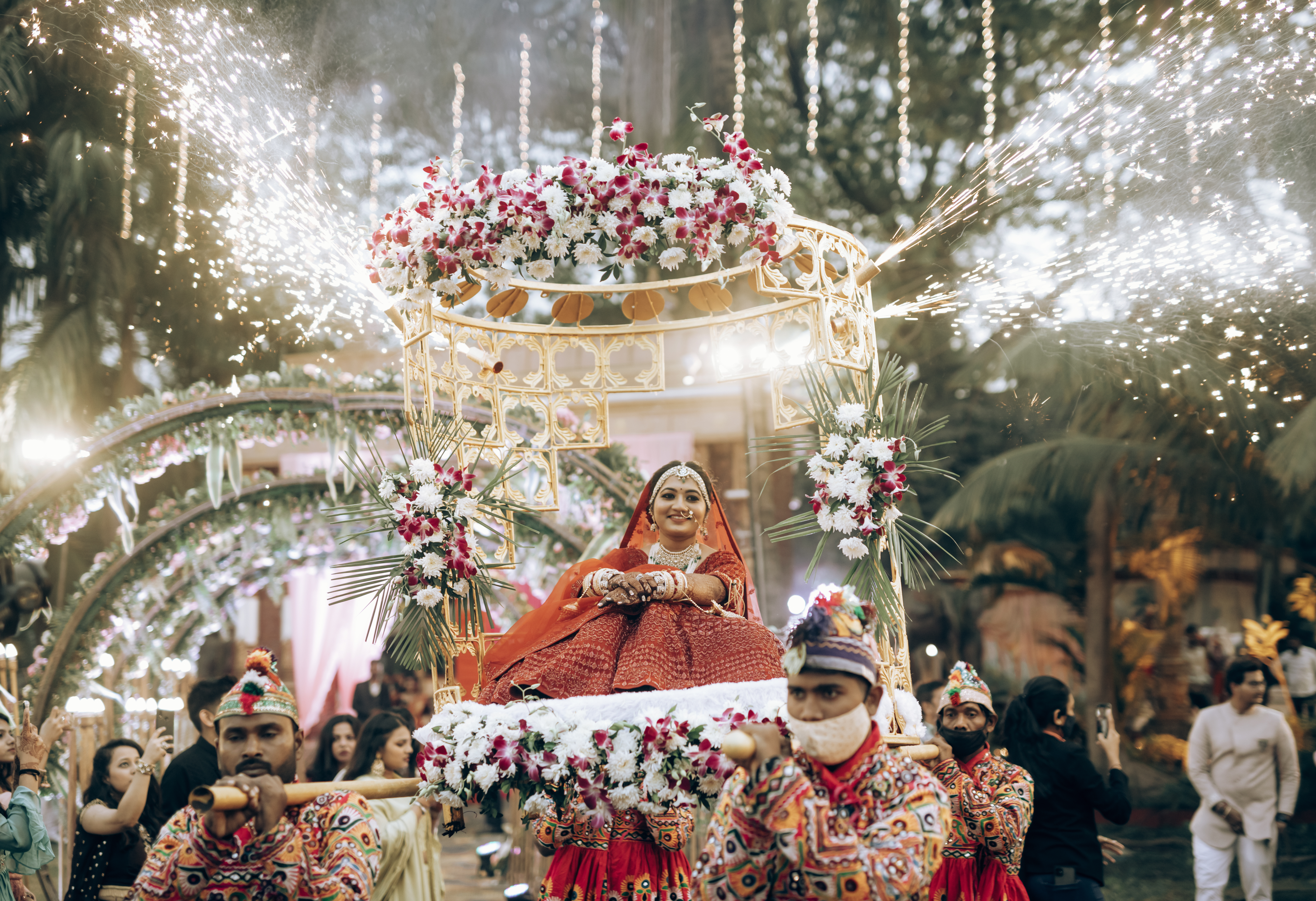 bride enters on a floral palki