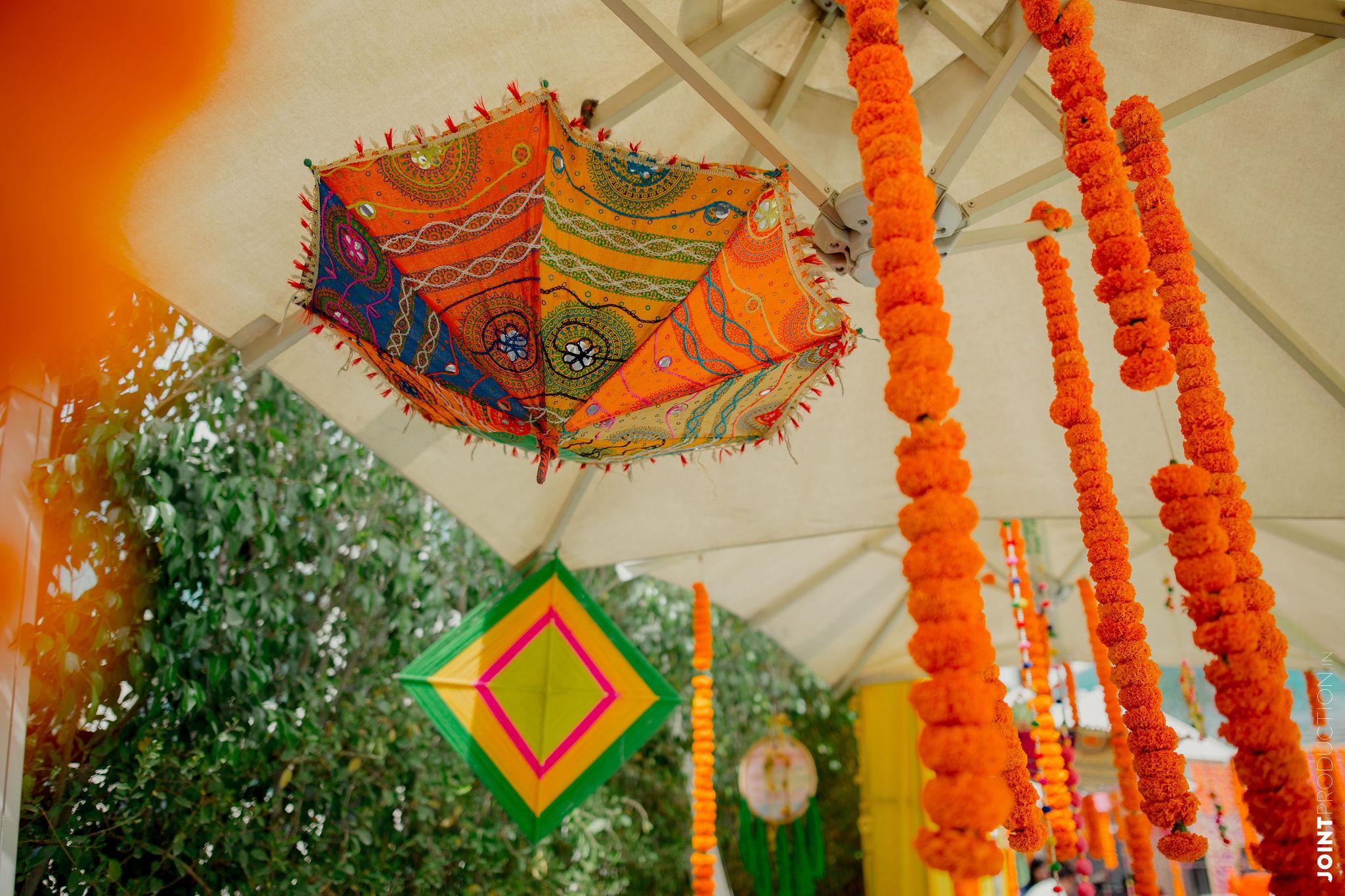 vibrant marigold and umbrella haldi decor